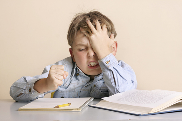 A frustrated child struggles with homework. Now, halfway through the school year, is the time to assess your child's progress and difficulties in school and try to help them enjoy learning.