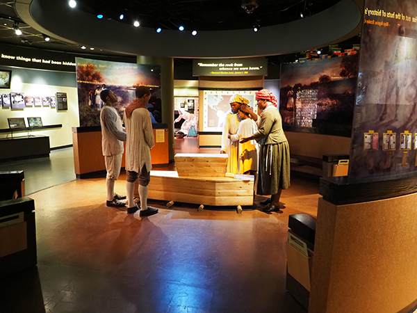 Photo of the exhibit at the African Burial Ground National Monument depicting five mourners gathered around two coffins.