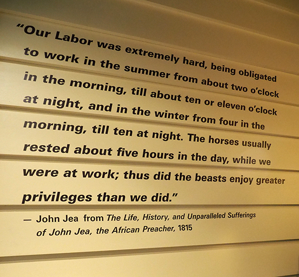 "Photo of a wall exhibit at the African Burial Ground National Monument featuring a quote from John Jea's 1815 work ""The Life, History, and Unparalleled Sufferings of John Jea, the African Preacher."" It reads, ""Our Labor was extremely hard, being obligated to work in the summer form about two o'clock in the morning, till abut ten or eleven o'clock at night, and in the winter from four in the morning, till ten at night. The horses usually rested about five hours in the day, while we were at work; thus did the beasts enjoy greater privileges than we did."""