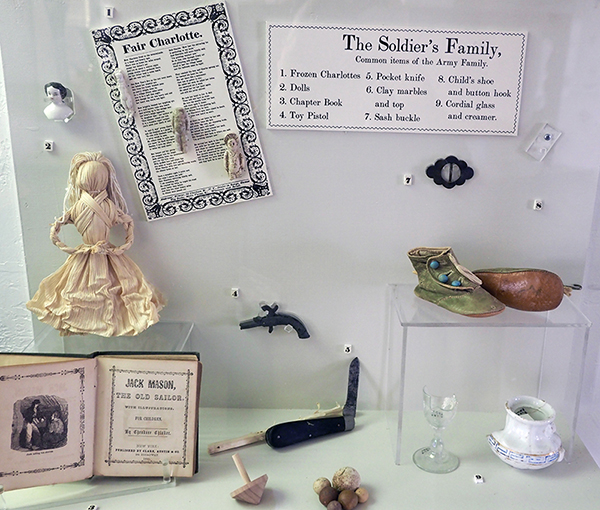 A collection of common items that might have been owned by an army family during the late 1800s at Fort McKavett, including corn husk dolls, frozen Charlotte dolls, toy pistols, chapter books, a child's shoe, clay marbles, a wooden top, a pocket knife, and more.