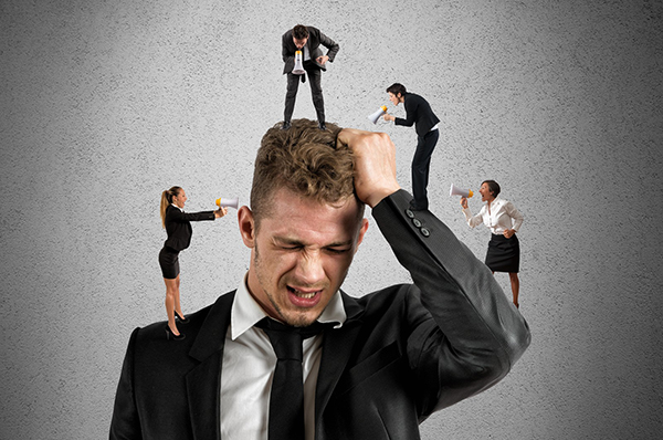 A man in a suit grabs his hair as many small people are perched on his arms, shoulders, and head, shouting at him through megaphones. This symbolizes the feeling of an overloaded brain that all of us, but especially dyslexics often feel. This blog offers some suggestions for brain management to help with that feeling.