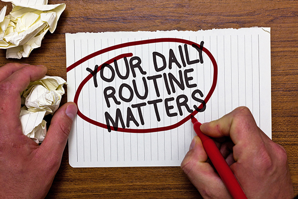 "Man writing on paper and circling with red pen the quote ""Your daily routine matters."" Blog by children's author Don M. Winn."